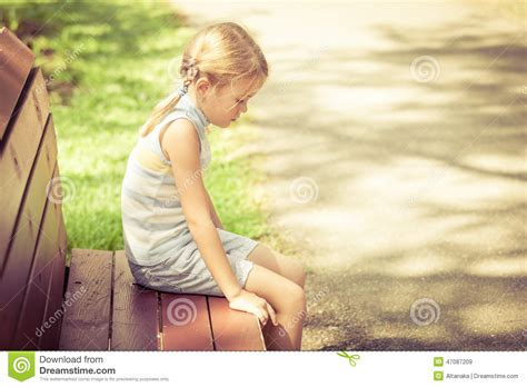 Sad Little Girl Sitting On Bench In The Park Stock Image